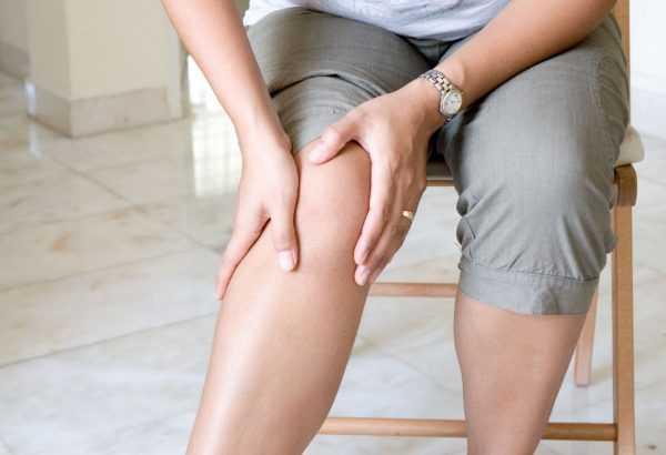 Женщина ощупывает свои ноги