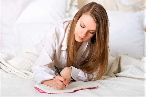 Женщина пишет в кровати