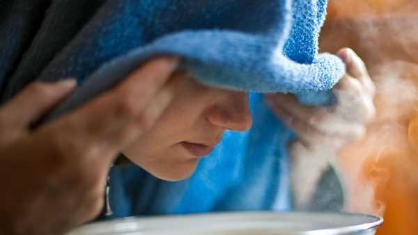 Женщина, покрыв голову полотенцем, дышит паром над кастрюлей