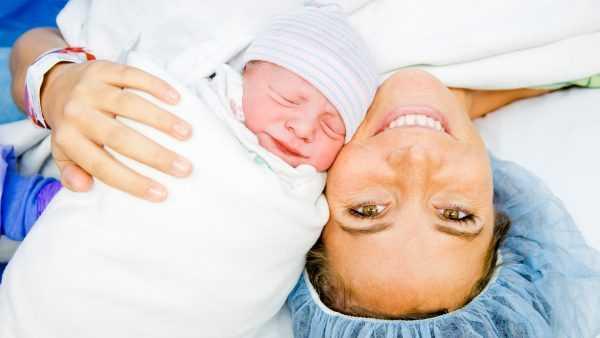 Женщина после родов с новорождённым лежат лицом к лицу