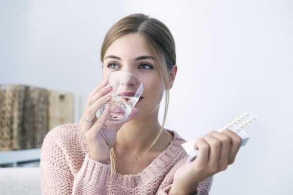 Женщина принимает противозачаточную таблетку