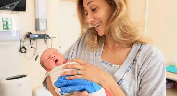 женщина с новорождённым на руках в роддоме
