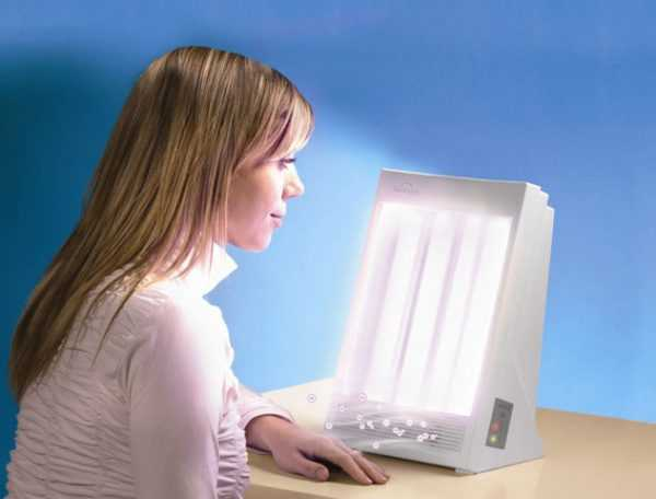 Женщина сидит перед лампой, имитирующей солнечный свет