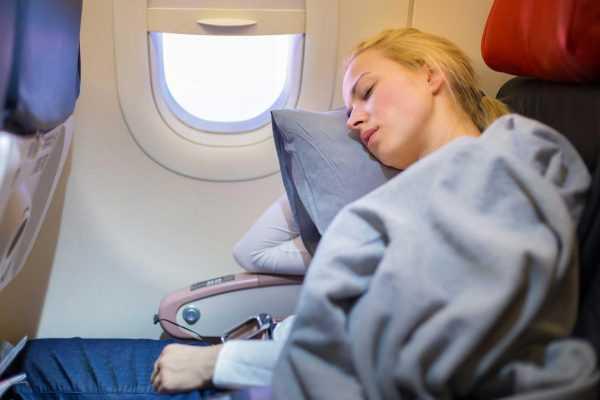 Женщина спит в салоне самолёта