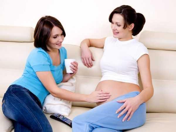 Женщина трогает живот беременной