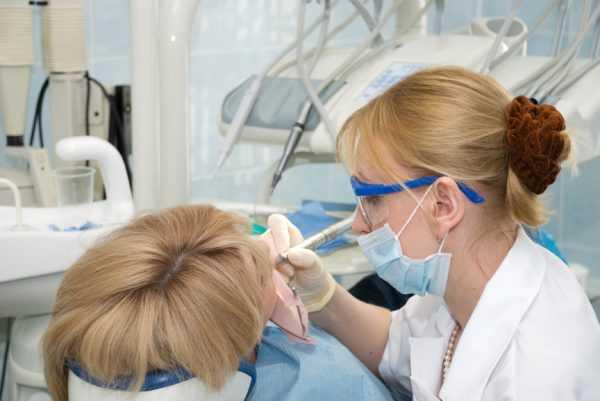 Стоматолог лечит зуб у девушки