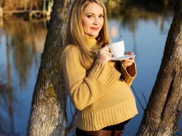 Беременная женщина на природе с чашкой в руке