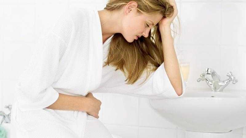 Женщина в белом халате сидит, опершись рукой на раковину в ванной