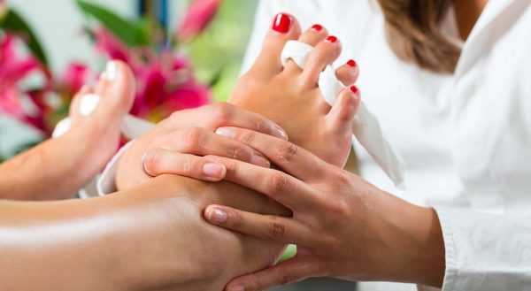Женщине делают массаж ступней