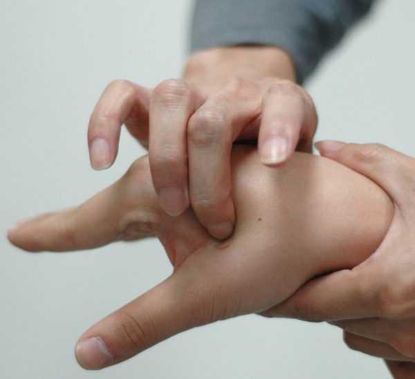 Женщине надавливают на точку между большим и указательным пальцами на руке