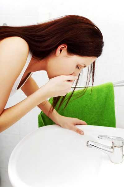 Женщина прикрывает рот рукой и опирается на раковину
