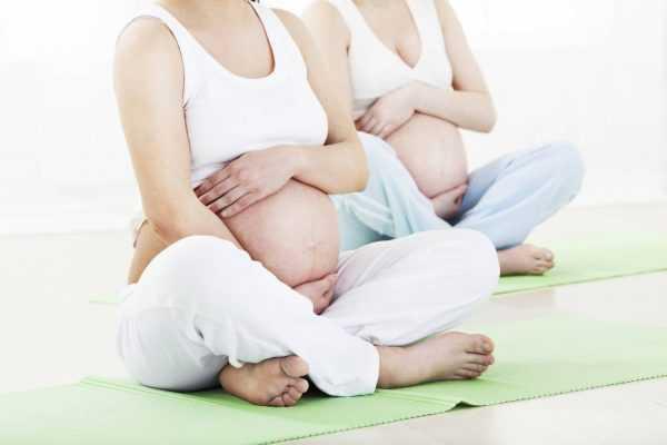 Две беременные женщины сидят в позе лотоса